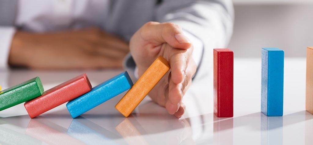 mão interrompe dominós caindo demonstrando a ação da empatia nas empresas